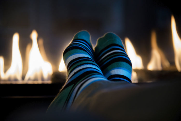 Low Section Of Person Wearing Socks By Fireplace