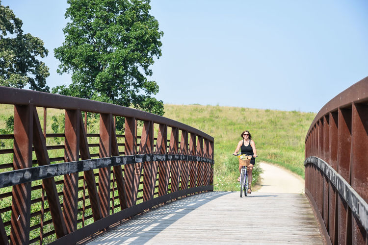 Man riding bicycle on footbridge