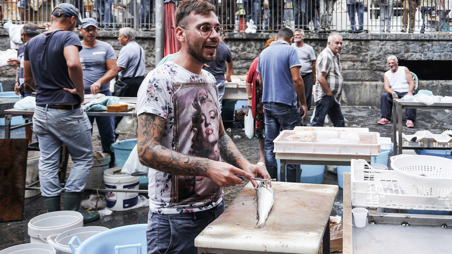 fish vendor in Catania, Sicily, Italy Occupation Standing Working Real People Group Of People Work Tool Fish Fish Market Catania Sicily Streetphotography Street Photography Madonna Laughing Man At Work