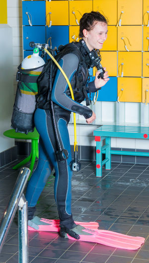 Smiling Woman In Diving Suit Walking On Floor