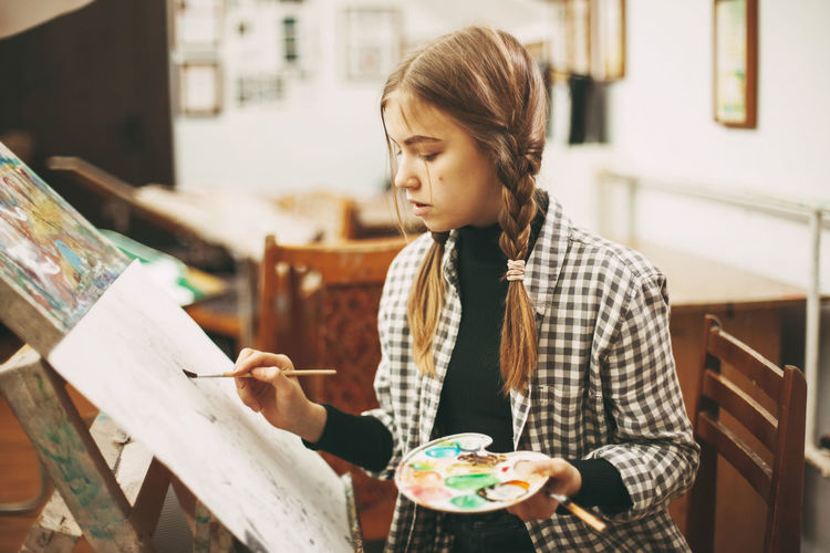 Beautiful teenage girl at art school with brush in hands, holding