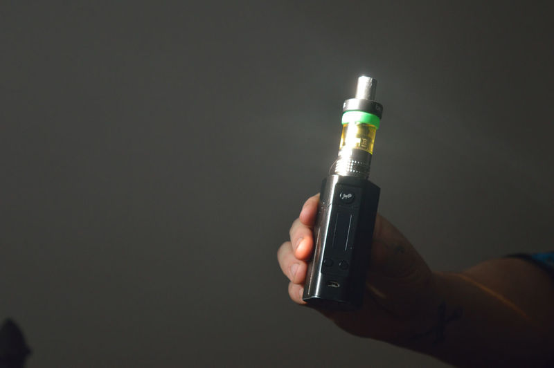 Cropped image of person holding electronic cigarette