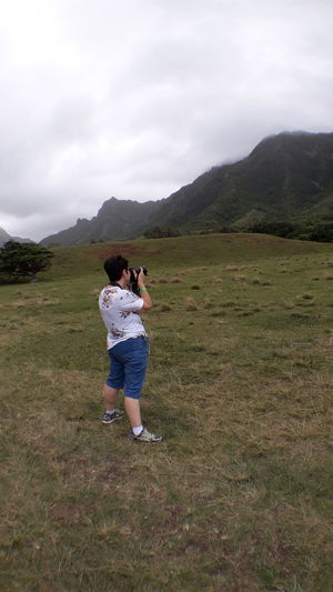 Full length of woman photographing on field against sky
