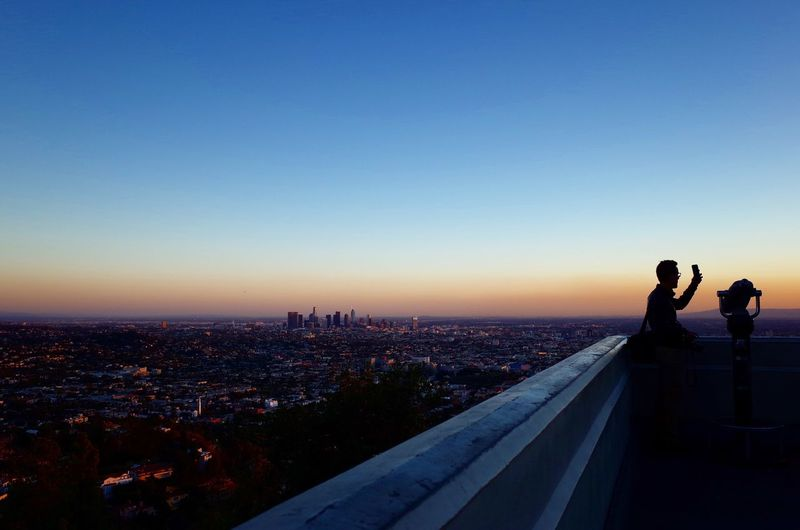 Man and cityscape against clear sky during sunset