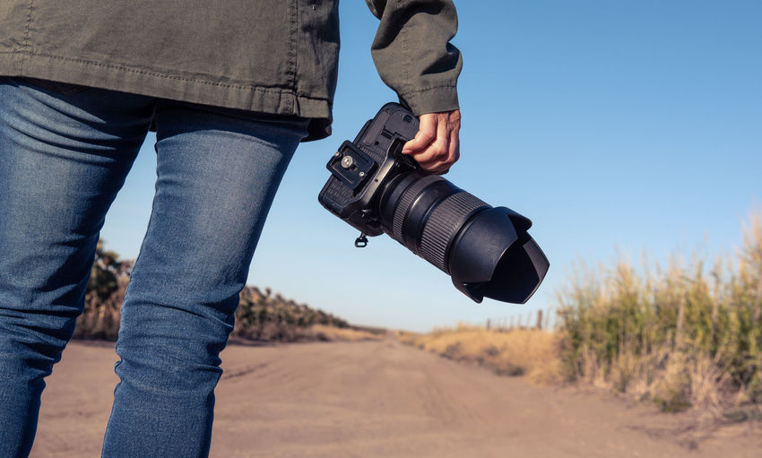 Midsection of woman holding camera while standing outdoors