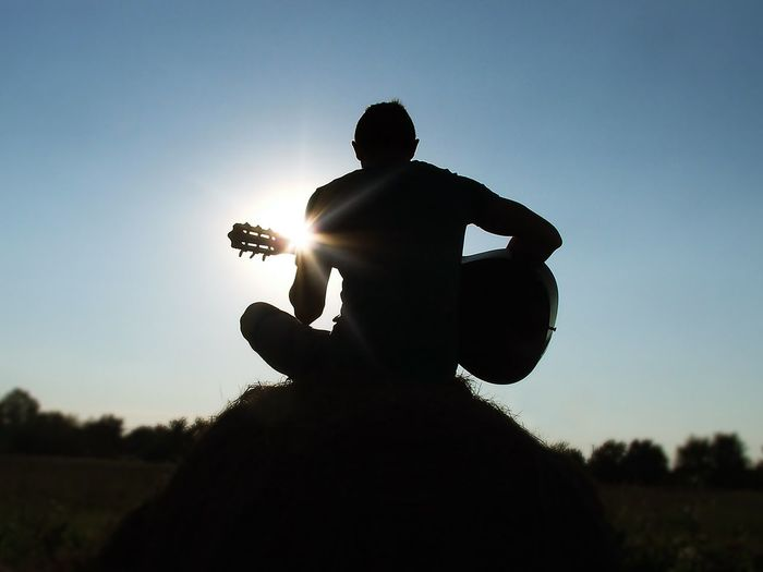 Back Lit Beauty In Nature Boy Bright Field Grass Guitar Happiness Home Is Where The Art Is Landscape Leisure Activity Lifestyles Music Nature Outdoors Plant Positive Scenics Sky Sun Sunbeam Sunlight Sunset Tranquil Scene Tranquility
