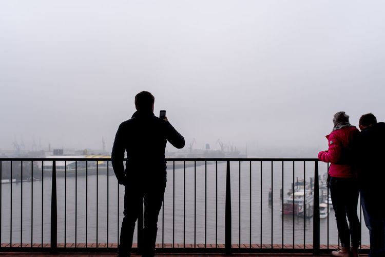 Rear view of people looking at harbor against sky during foggy weather