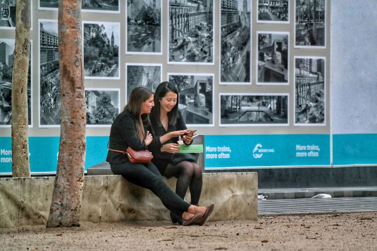 Full Length Sitting Wireless Technology Outdoors Togetherness Adults Only Day People Bonding Together Resting Relaxing Chilling Out Street Life People Watching Seated Street Bench People Photography Melbourne City Street Photography Discussion Chatting Sitting candidly The City Light human