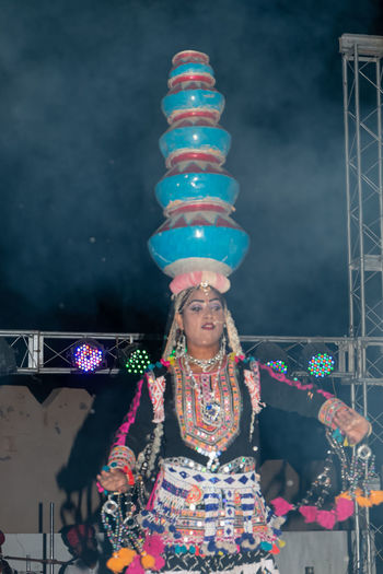 Midsection of woman with illuminated lighting equipment at night