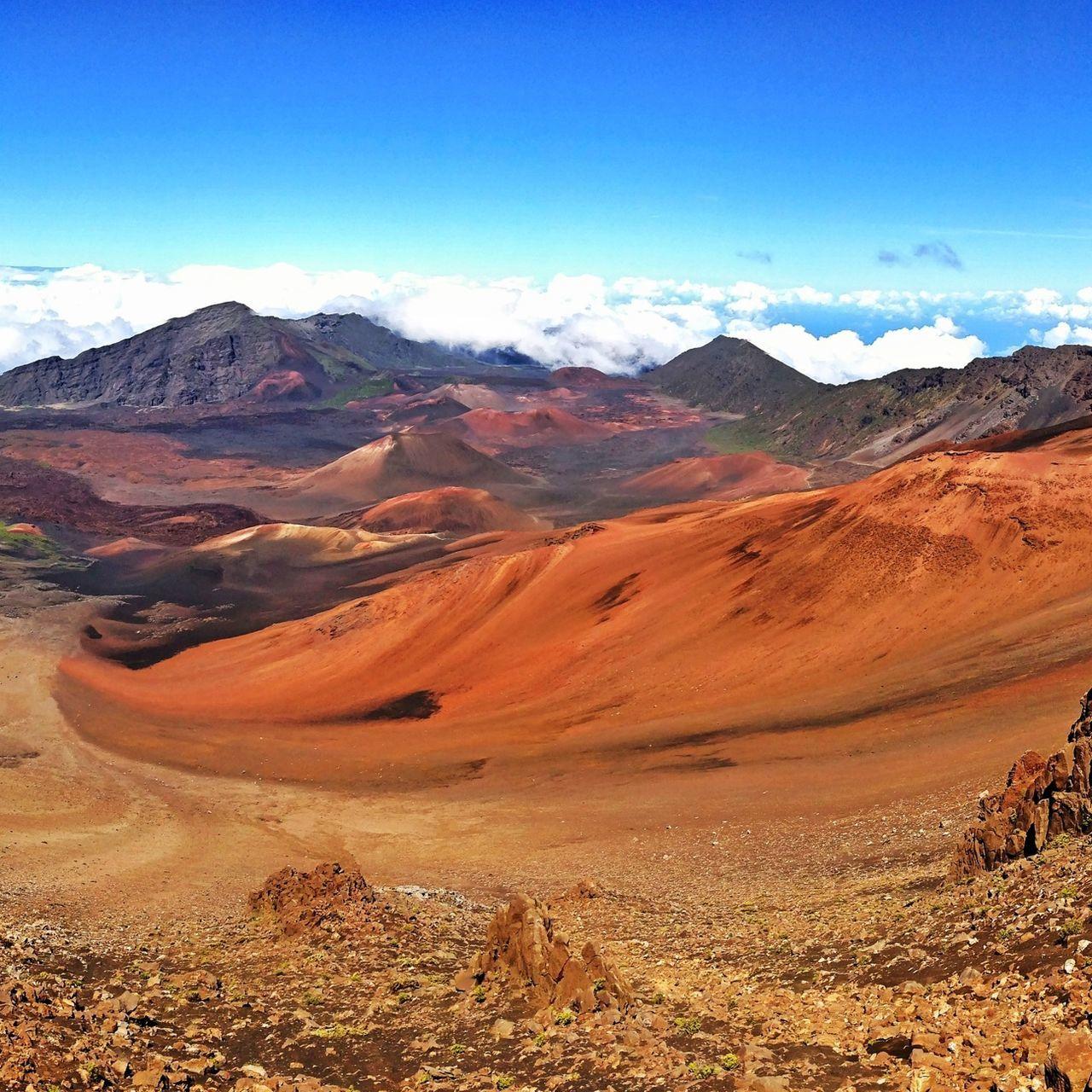 Barren landscape against mountain range and blue sky