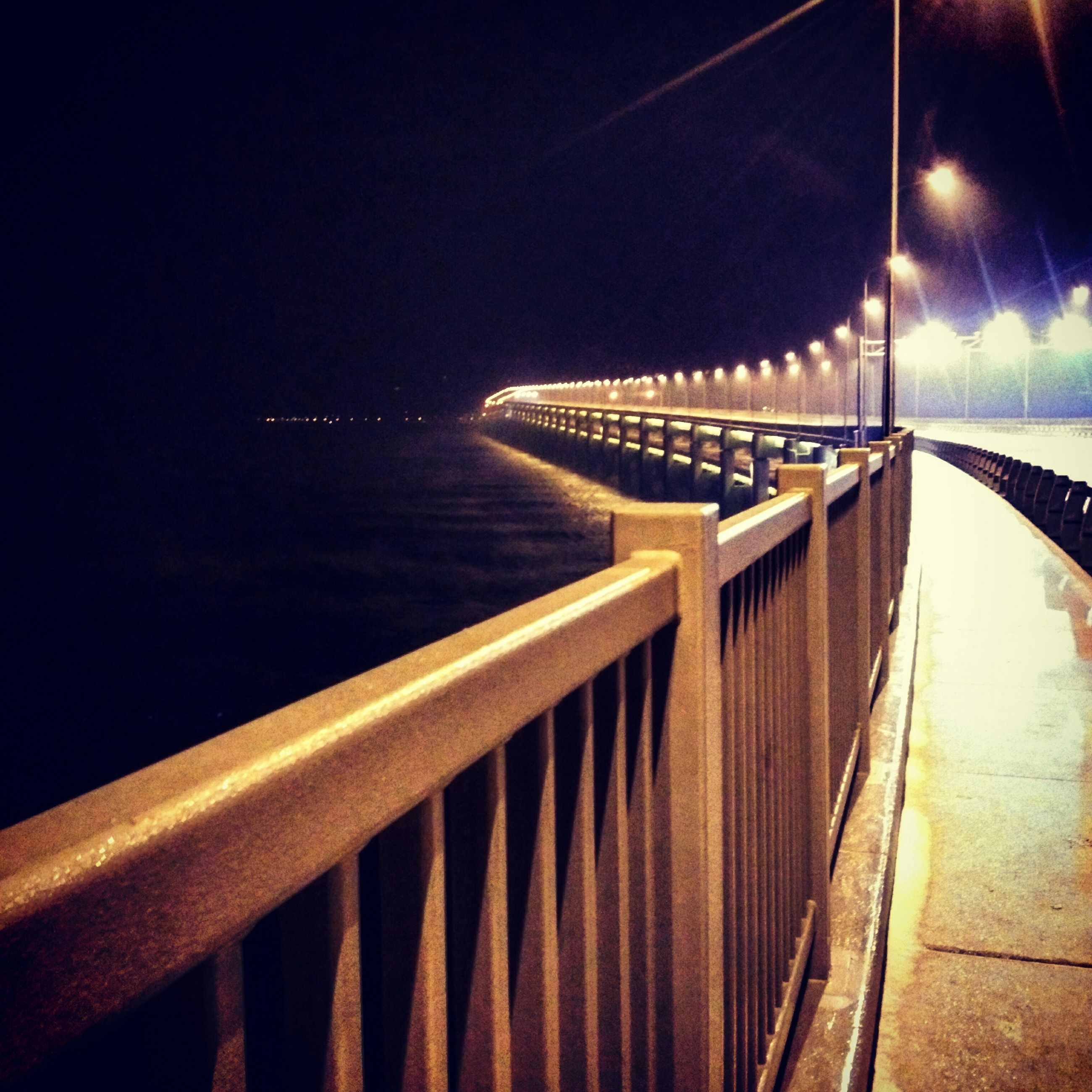 illuminated, transportation, railing, the way forward, night, built structure, empty, diminishing perspective, architecture, connection, long, water, no people, bridge - man made structure, absence, pier, lighting equipment, bridge, outdoors, copy space