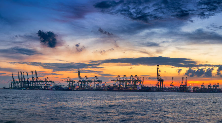 Cranes By Sea Against Cloudy Sky During Sunset