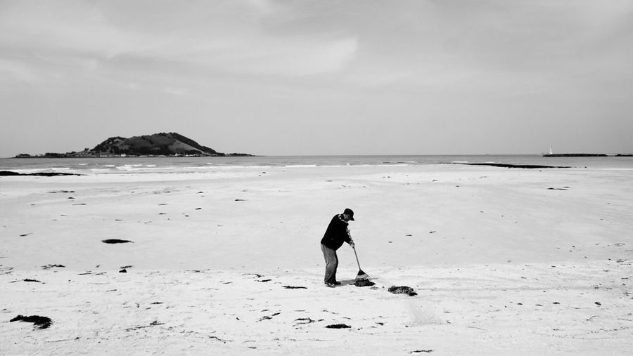Man sweeping at beach against sky