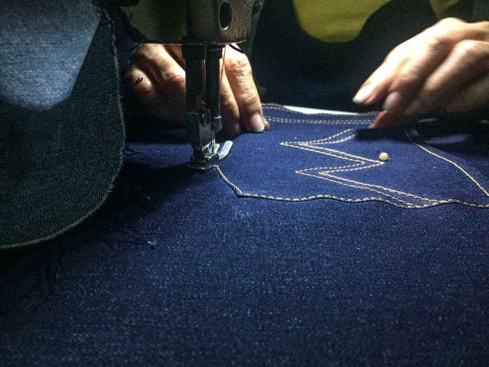 Cropped hands sewing jeans on machine