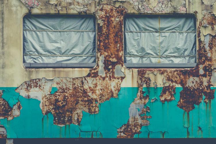 Windows of weathered train covered with tarpaulin