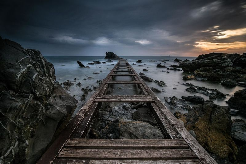 Damaged boardwalk at sea shore against cloudy sky during sunset