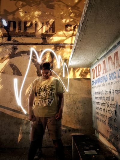 Full length of man standing on illuminated wall