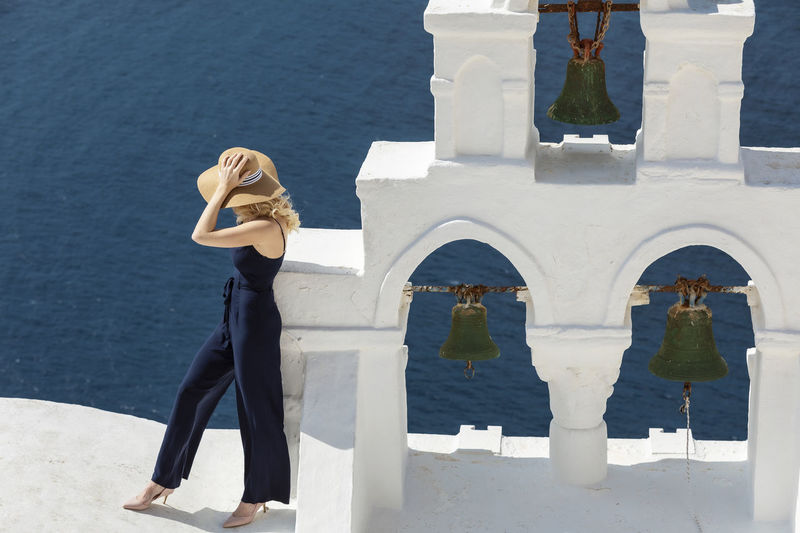 Woman standing on building against sea