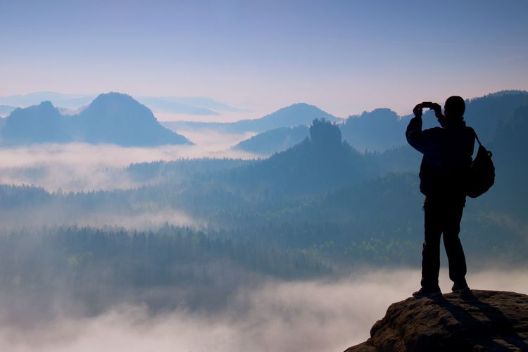 Tourist with backpack takes photos with smart phone on the rocky peak. dreamy fogy valley below