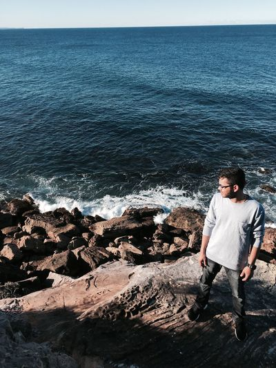 High Angle View Of Young Man Standing On Rock By Sea Against Sky