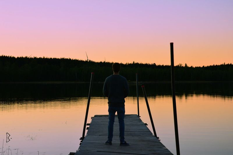 Rear view of silhouette man standing on lake against sky