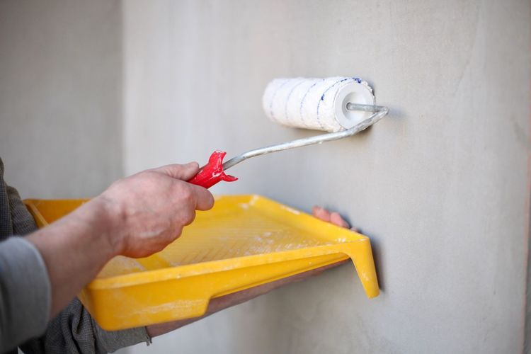 Midsection of man working against wall at home
