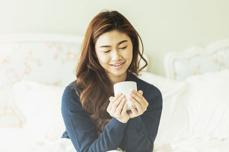 Beautiful Attractive Asian woman smile and holding coffee cup on bed in bedroom feeling so fresh and happiness in the morning Adult Attractive Beautiful Young Adult One Person Holding Smiling Young Women Food And Drink Cup Front View Lifestyles Happiness Indoors  Mug Drink Coffee - Drink Leisure Activity Coffee Focus On Foreground Coffee Cup Waist Up Women Hairstyle Drinking Hair Hot Drink Beautiful Woman Beauty Bed Bedroom Book Breakfast Casual Cheerful Chinese Coffee Cute Fashion Female Fresh Girl Happy Home Hot Hotel Indian Indoors  Interior Korean