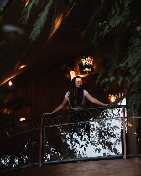 One Person Young Adult Real People Leisure Activity Lifestyles Portrait Plant Women Front View Adult Tree Young Women Nature Beautiful Woman Night Lights Twilight Lantern Cabin Balcony Forest Fairy Tale Reflection Nature Photography Wooded Area Summer