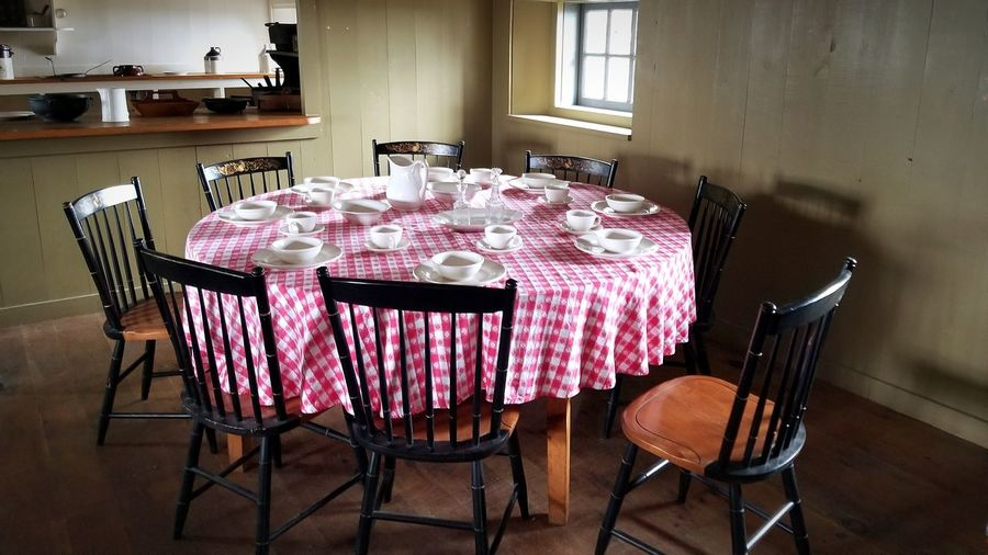 Place setting on table amidst chairs at home