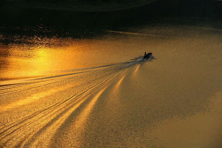 High angle view of speedboat moving in river during sunset