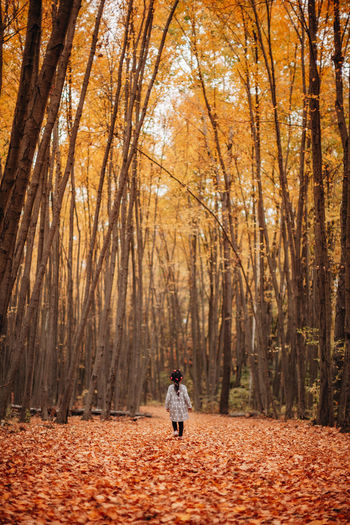 Girl standing by trees in forest during autumn