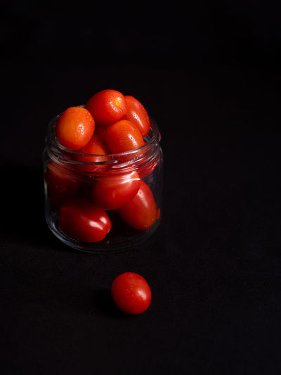 Close-up of tomatoes in glass jar on table against black background