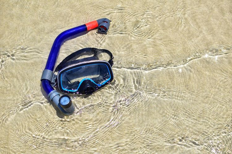 Mask and tube for snorkeling lying on the sandy beach with slow on sandy texture and Summer vacation swimming concept. Holiday Relaxing Scuba Diving Snorkeling Swimming Textured  Tube Vacations Wave Adventure Backgrounds Blue High Angle View Leisure Activity Mask Nature Outdoors Sand Sandy Sea Snorkel Summer Sunlight Travel Destinations Water