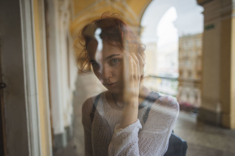 Portrait of young woman looking away while standing against window