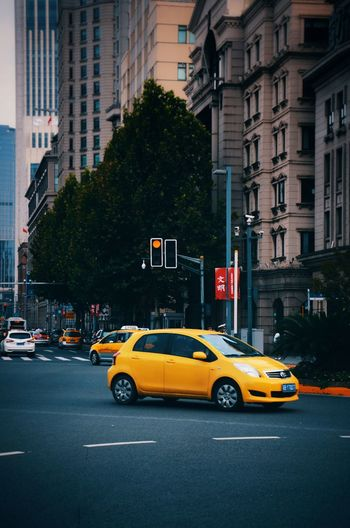 Yellow Taxi Taxi City Street Building Exterior Architecture Traffic Outdoors Travel Illuminated Skyscraper Multi Colored No People Neon Travel Destinations City Life Tree Day City Yellow Car