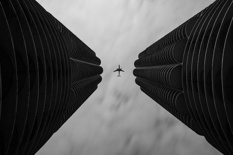 Low angle view of modern buildings against sky with airplane