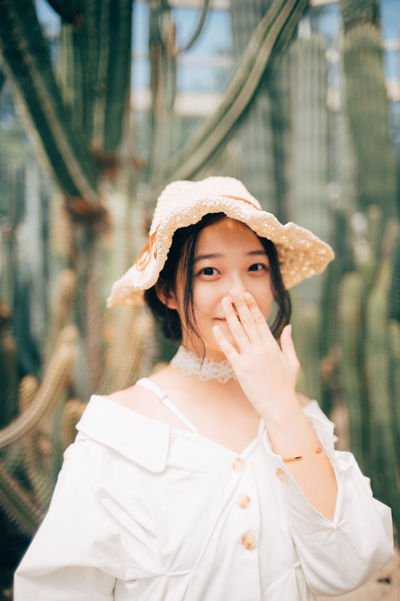 shy Asian  Adult Beautiful Woman Casual Clothing Clothing Day Focus On Foreground Front View Hairstyle Hat Leisure Activity Lifestyles Looking At Camera One Person Outdoors Portrait Real People Standing Waist Up Women Young Adult Young Women