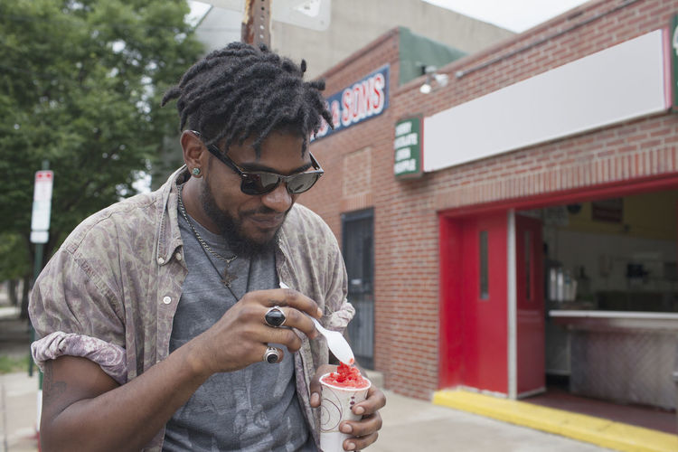Young man looking away while holding ice cream in city