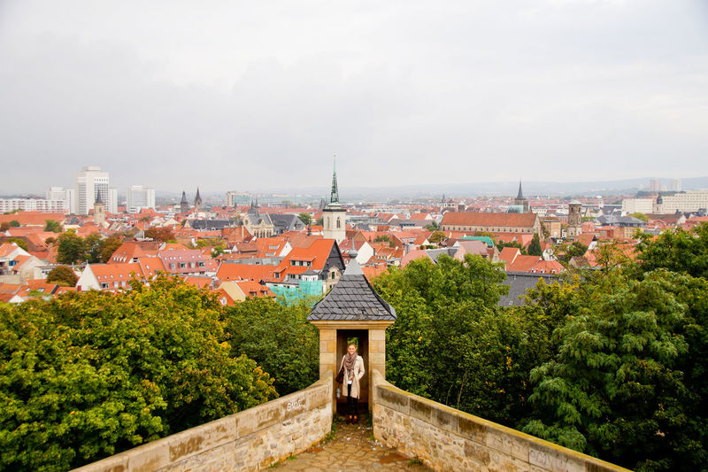 High Angle View Of Woman On Terrace Against Cityscape