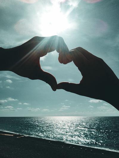 Heart shape over sea against sky