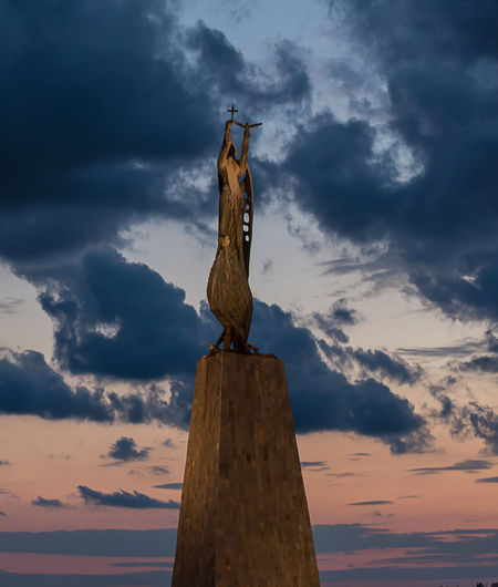 Low angle view of jesus christ against cloudy sky during sunset