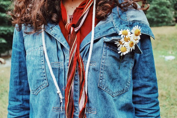 Midsection of woman wearing denim jacket with flowers on field