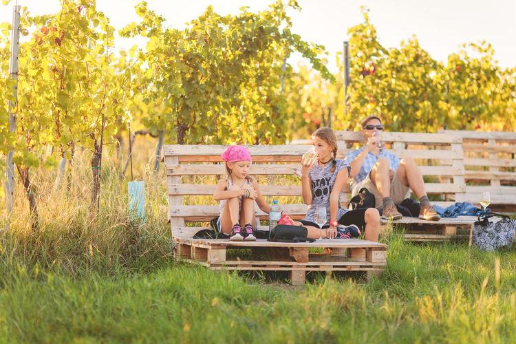 Family sitting on bench in vineyard