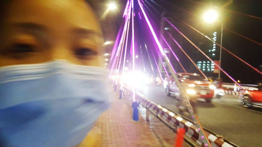 Who, me? Girl on bridge in Da Nang, Vietnam. Blurred Motion Nightlife Outdoors Vietnam Street Đà Nẵng Bridges Traffic Girls Facemasks Moments