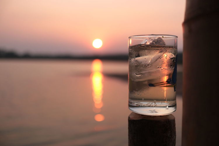 Close-up of glass of water during sunset