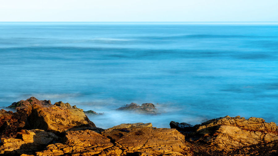 Long exposure view of the ocean near Pebble Beach, Monterey, California,, USA, on the 17-mile drive route in the winter of 2019, in the sunrise- large blue copy space Sea Rock Water Rock - Object Solid Beauty In Nature Scenics - Nature Sky Tranquil Scene Horizon Nature Land Horizon Over Water Tranquility No People Day Non-urban Scene Idyllic Motion Outdoors Power In Nature Long Exposure Photography Pebble Beach,Ca Monterey Bay 17-Mile Drive Sunrise Copy Space Over Ocean