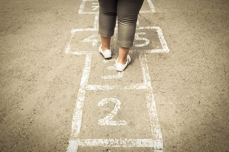 Low section of girl playing hopscotch on road