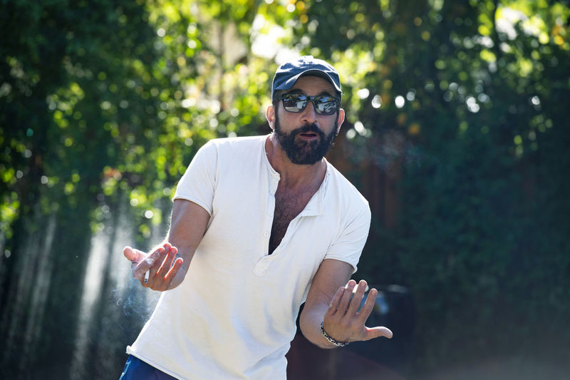 Man wearing sunglasses smoking cigarette against trees
