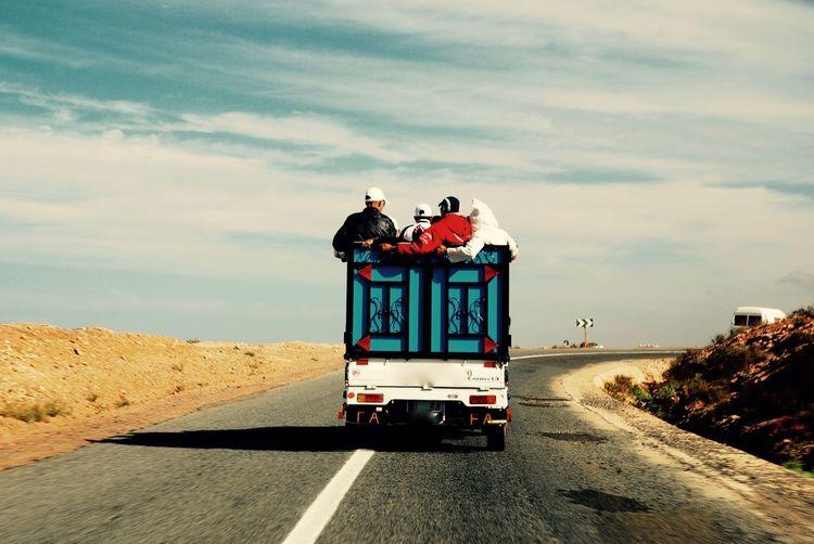 People In Vehicle On Road At Desert Against Sky