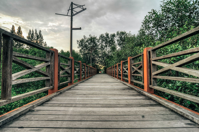 wooden footbridge and cloudy sky background Bridge Cloud - Sky Cloudy Day Footbridge Footbridge Nature No People Outdoors Sky Structure The Way Forward Tree Water Wood - Material Wooden